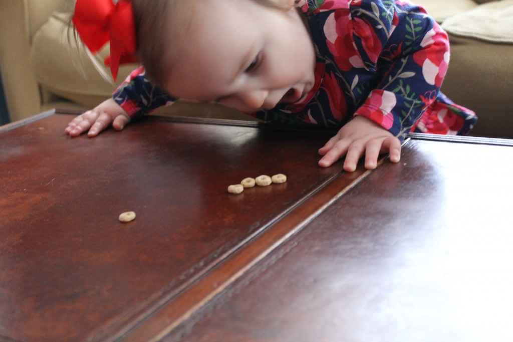 avery eating cheerios off table